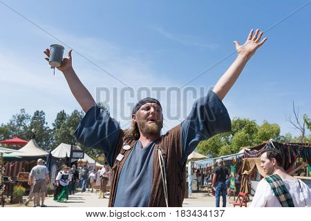 Participant With A Mug In Hand And Arms Raised