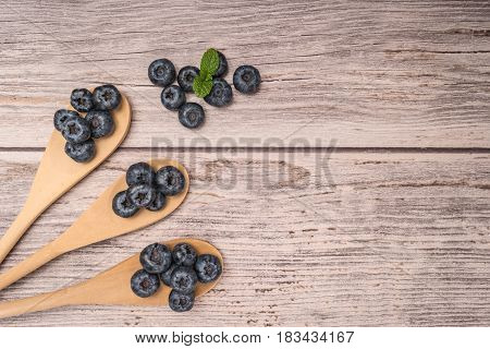 Fresh blueberries with wooden spoon and mint leaf on rustic textured background. Top of view with copy space