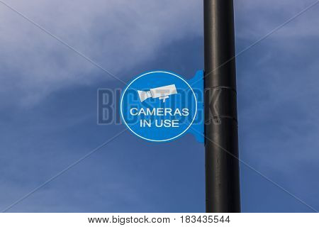 Blue Security Camera In Use Sign on Black Post and Partly Sunny Background III