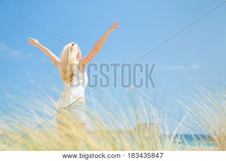 Relaxed woman, arms raised, enjoying sun, freedom and life an a beautiful beach. Young lady feeling free, relaxed and happy. Concept of vacations, freedom, happiness, enjoyment and well being.
