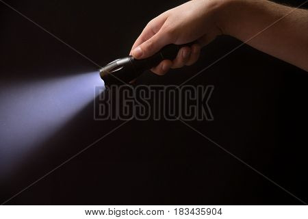 The Flashlight In The Man's Hand From The Right Upper Corner , Isolated On Black Background