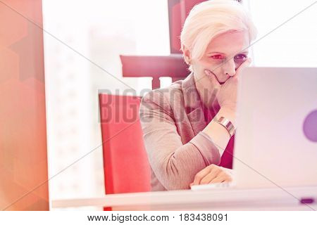 Serious mature businesswoman using laptop at desk in office