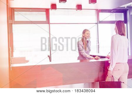 Young female receptionist looking at businesswoman signing document in office