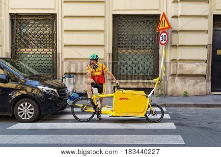 ROME ITALY - April 4 2017: On duty Italian DHL Postman with his delivery bicycle using mobile phone to distributes parcel.
