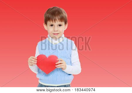 Cute little boy holds in his hands a heart . Close-up.