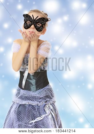 Slender little girl , with beautiful hair on his head, elegant long Princess dress.Posing in carnival mask.She sends a kiss.Blue Christmas festive background with white snowflakes.