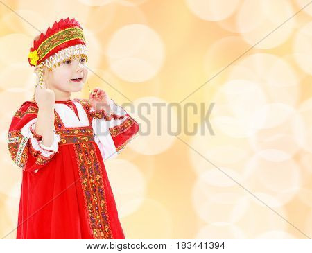 Cute little girl in Russian folk dress. She threatens with a finger.Brown festive, Christmas background with white snowflakes, circles.