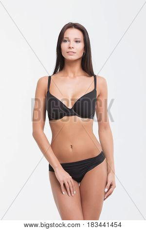 Sexy woman in a black lingerie on the white background.