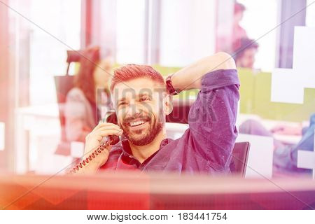 Smiling mid adult businessman talking on phone in office
