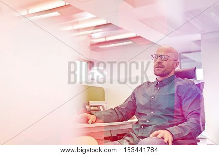 Mid adult businessman sitting on chair in office