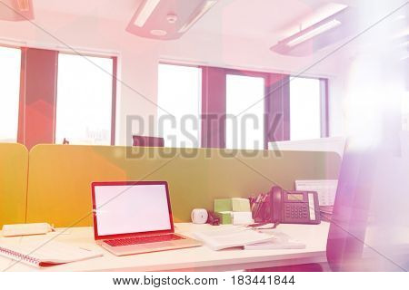 Laptop with spiral books and landline phone on desk at office
