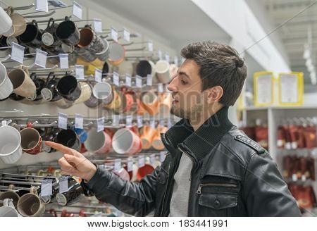 male customer choosing cups or mugs in supermarlet store.