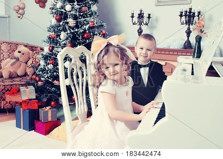 Solemnly dressed little boy and girl into the night, sitting at a white piano. Children put hands on the keys.Creative toning of a photograph.