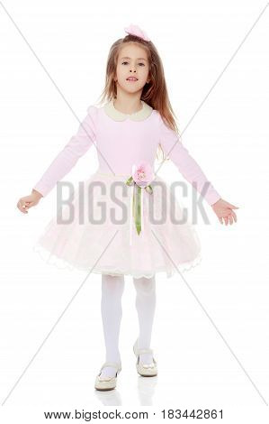 Dressy little girl long blonde hair, beautiful pink dress and a rose in her hair.She takes a step forward, spreading his hands widely.Isolated on white background.
