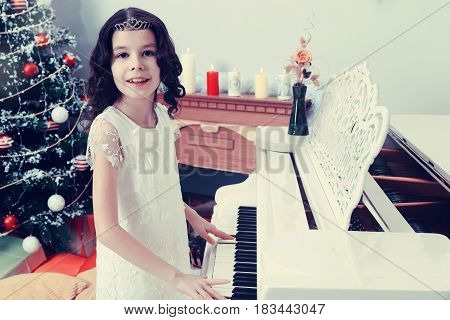 Adorable little girl new year's eve on the backdrop of the Christmas tree plays the piano.Creative toning of a photograph.