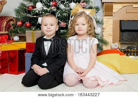 Well-dressed boy and girl sitting near a Christmas tree surrounded by gifts.