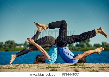 Athletic man and woman doing yoga poses together
