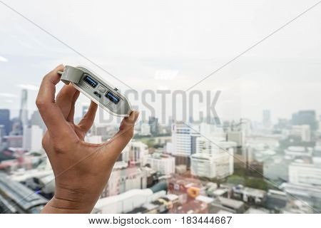 close up woman hold power bank supply energy to mobile phone with left hand