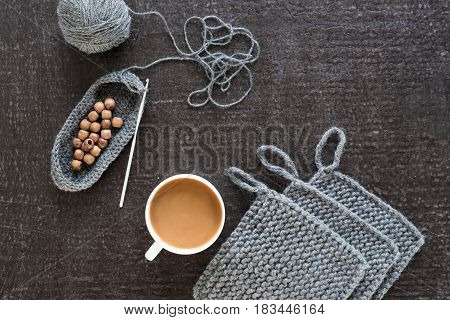 Cup of coffee, wooden beads and grey crocheting on a black background.