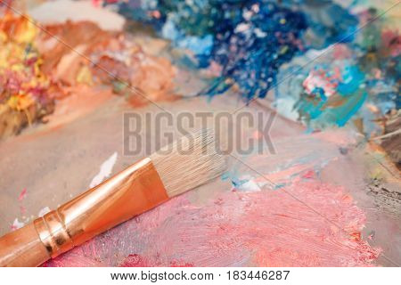 The brush lies on a wooden palette with oil paints. Art supplies. Creative expression tools.