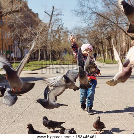 Little girl feeds pigeons. Spring mood. Outdoors.