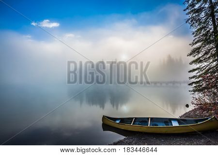 Fishing boats moored on the shore. Emerald Lake in Yoho National Park. Foggy morning