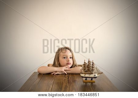 Dreamy 4-year-old girl sitting at a wooden table. A little boat standing on a table next to her. Natural light is used. Manipulated image with an added vignette.