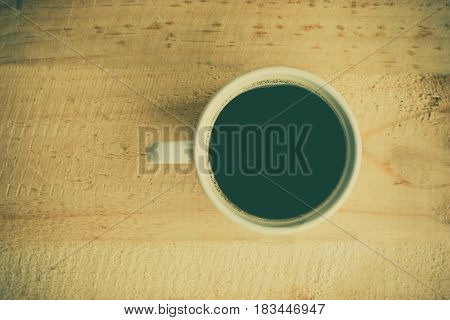 Topi view of cup of coffee on wooden table vintage tone.