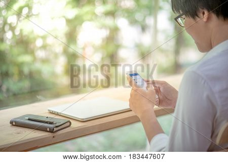 Young Asian business man texting message on social media application by phone casual professional entrepreneur using smartphone and laptop at home workspace modern lifestyle and digital age concepts