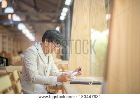 Young Asian casual business man using smartphone and checking his work at vintage cafe in the city smart urban lifestyle with digital device and technology gadget trends work life balance concepts