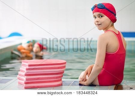 Elementary age girl wearing red swimsuit sitting on the edge of a swimming pool near pile of swimming floats looking at camera