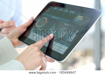 businesswoman showing graphs by finger at the digital tablet