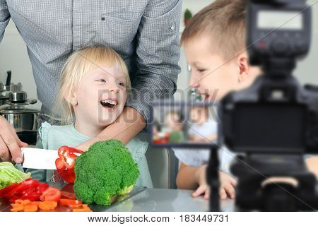 man with children filming the meal preparation. Home Video Camera, Blogging, Cooking, Domestic Kitchen
