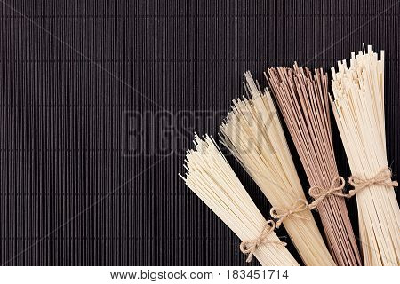 Bundles of raw noodles on black mat background with copy space top view.
