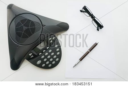 isolated top view of Voip IP conference phone with glasses and pen