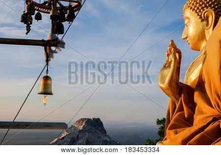 Blessing hand of praying buddhist monk's statue and big golden buddha at the background TIger Cave Temple Krabi province Thailand. Focus on the foreground hand.