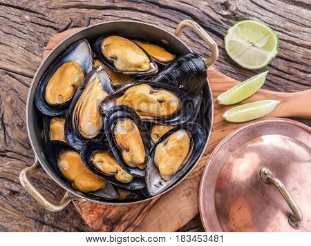 Boiled mussels in copper pan on the wooden table.