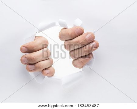 Man's hands tearing the hole on a paper.