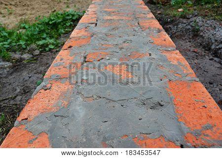 Bricklaying Brickwork. Installing red blocks and caulking brick masonry.