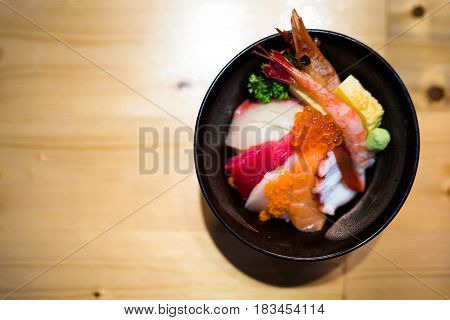 Chirashi sushi Japanese food rice bowl with raw salmon sashimi mixed seafood top view darken edge copy space on wooden table focus on salmon eggs with depth of field effect
