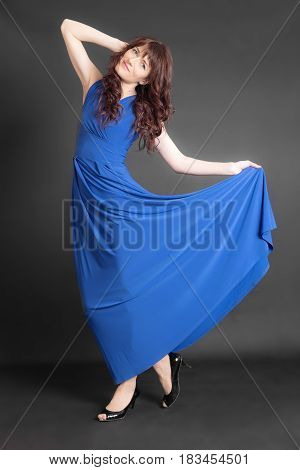Slender woman in a blue dress on a black background