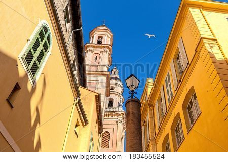 Belfry of Saint-Michel Archange basilica among colorful houses under blu sky in old town of Menton, France.