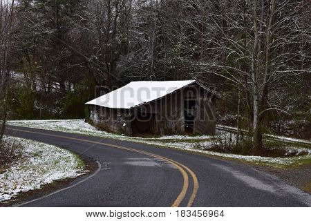 Curvy road leading past a rural barn with a dusting of snow.