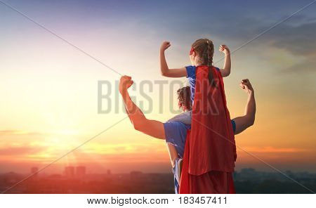 Happy loving family. Dad and his daughter playing outdoors. Daddy and child girl in an Superhero's costumes. Concept of Father's day.
