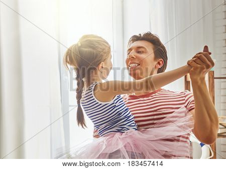 Happy father's day! Dad and his daughter child girl are playing, smiling and dancing. Family holiday and togetherness.