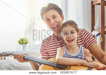 Happy father's day! Dad and his daughter child girl are playing guitar together. Family holiday and togetherness.