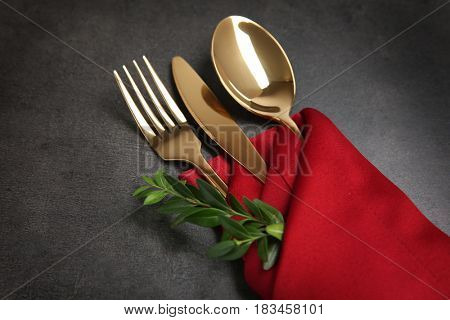 Table setting with golden cutlery in red napkin on grunge background