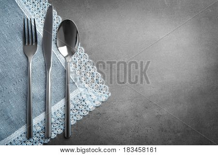 Table setting with silver cutlery and napkin on grunge background