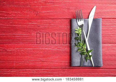 Table setting with cutlery and napkin on red background