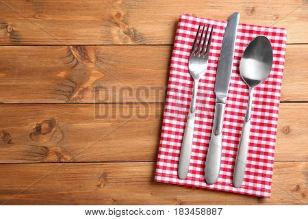 Table setting with silver cutlery and napkin on wooden background